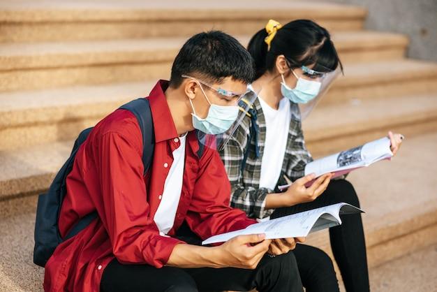 Männliche und weibliche studenten, die masken tragen, sitzen und lesen bücher auf der treppe