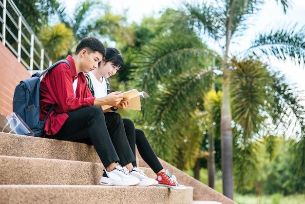 Männliche und weibliche studenten sitzen und lesen bücher auf der treppe.