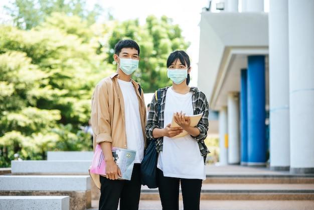 Männliche und weibliche studenten tragen eine gesundheitsmaske und sprechen auf der treppe miteinander.