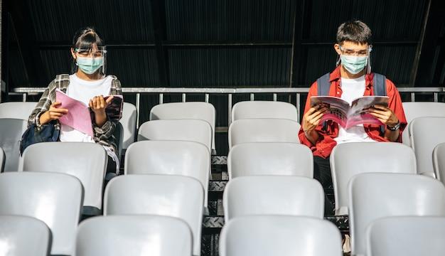 Männliche und weibliche studenten tragen masken und sitzen und lesen auf dem feldstuhl
