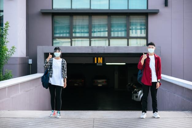 Männliche und weibliche studenten tragen masken und stehen vor der universität.