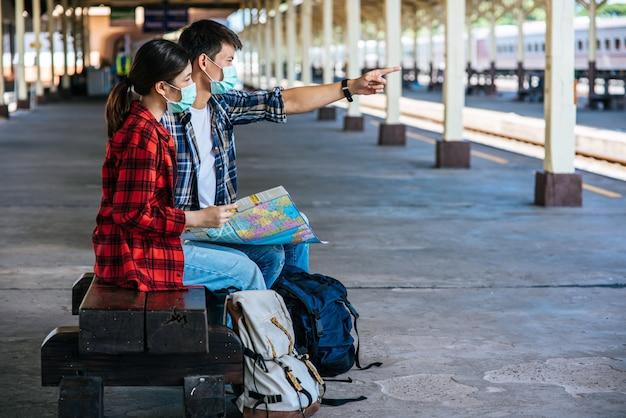 Männliche und weibliche touristen schauen auf die karte neben der eisenbahn.
