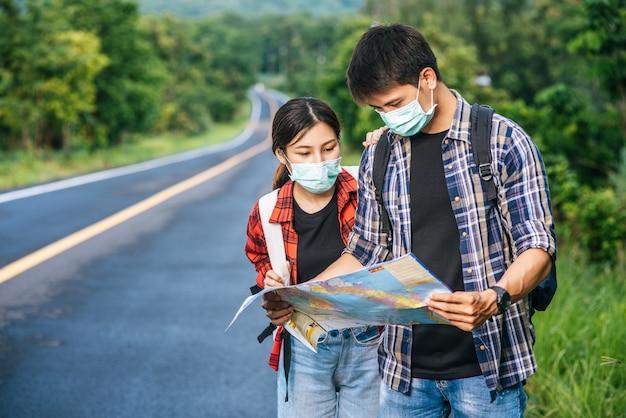 Männliche und weibliche touristen tragen medizinische masken und schauen auf die karte auf der straße.