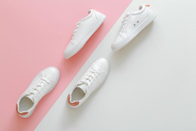 Männliche und weibliche weiße turnschuhe auf rosafarbenem hintergrund. weiße lederschuhe mit schnürsenkeln mit kopierraum. zwei paar stylische sneaker bequeme sportswear hipster damenschuhe.