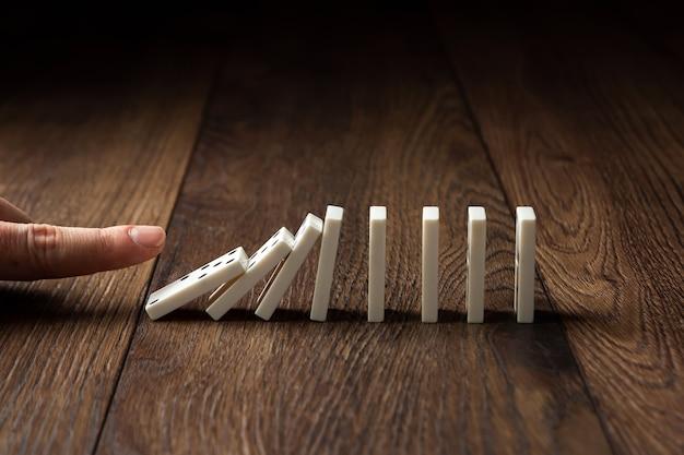 Männliche von hand eindrückende weiße dominos auf einem braunen holz