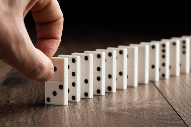 Männliche von hand eindrückende weiße dominos