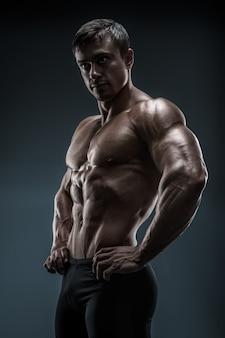 Männliche vorbildliche aufstellung der muskulösen und geeigneten jungen bodybuildereignung.
