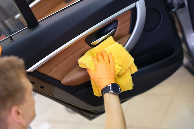 Männliche waschmaschine in handschuhen wischt autotür mit mikrofaser-nahaufnahme ab