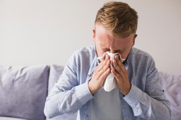 Männliche wehende nase mit taschentuch auf sofa