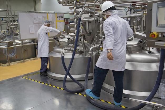Männliche zwei arbeiten den prozess der cremekosmetischen fermentation bei der herstellung mit edelstahltank