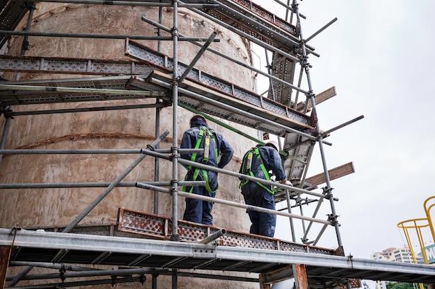 Männliche zwei arbeiter, die den ersten sicherheitsgurt tragen und an einem hohen gerüstplatz auf dem oberen tanköl arbeiten