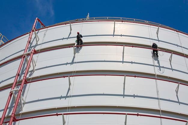 Männliche zwei arbeiter in der höhe der tankoberteilplatte seilleiterzugangssicherheitsinspektion des dickenspeichertanks gaspropan.