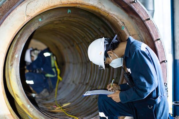 Männliche zwei arbeiter inspektion maß die kreisförmige dicke der rohrschlange des kessels scannen minimale dicke in gefahr beengten raum.