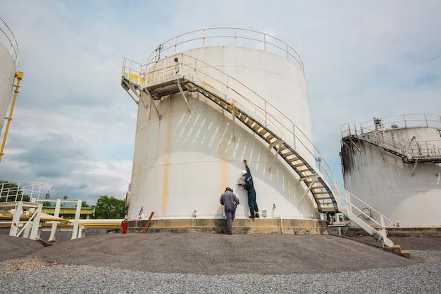 Männliche zwei arbeiter inspektion scan-tank des vertikalen chemischen tanköls der dickenplatte.
