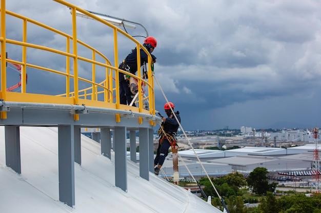 Männliche zwei arbeiter kontrollieren das seil nach unten auf dem dach des tanks seilzugangsinspektion der dicke der shell-platte-lagertank-gas-hintergrundwolkensturm.