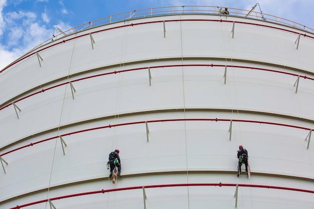Männliche zwei arbeiter kontrollieren das seil nach unten auf dem dach des tanks seilzugangsinspektion der dickenmantelplatte des lagertanks gassicherheitsarbeiten in der höhe.