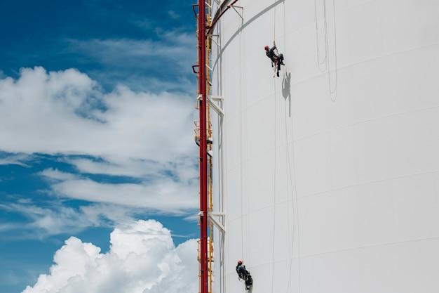 Männliche zwei arbeiter kontrollieren die inspektion des seilzugangs in der höhe des tanks von der dicke der pipeline und des tankgases am blauen himmel.