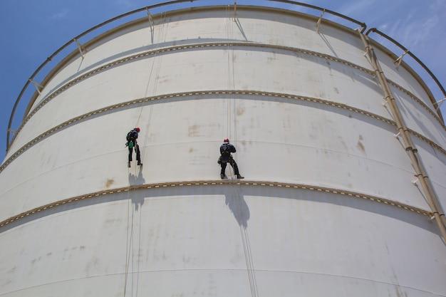 Männliche zwei arbeiter seilzugangsinspektion der dickenspeicher-weißtankindustrie