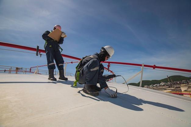 Männliche zwei arbeiter sind für die inspektion der ultraschalldicken-dachplattenkuppel oben des lagertanks.