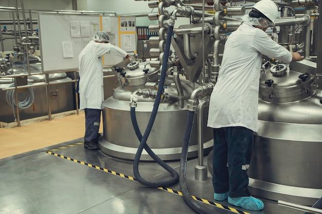 Männliche zwei arbeitsbetriebe verarbeiten milchpulverkeller in der fabrik mit vertikalen edelstahltanks