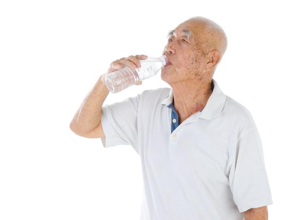 Männlicher älterer bürger, der mineralwasser trinkt