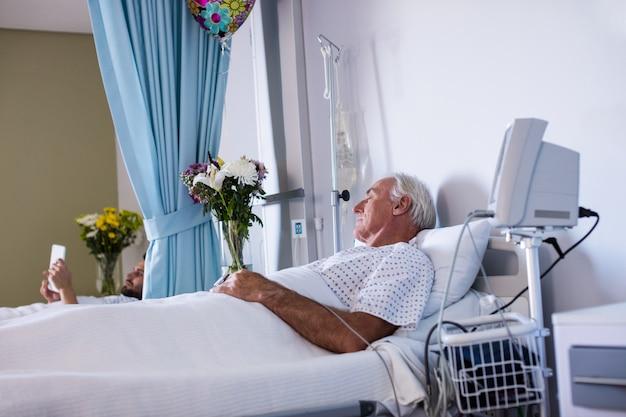 Männlicher älterer patient, der sich in der station entspannt
