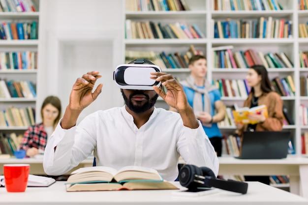Männlicher afrikanischer student, der vr-brille in der öffentlichen bibliothek benutzt und mit virtuellem lehrbuch zur vorbereitung auf prüfung oder test arbeitet