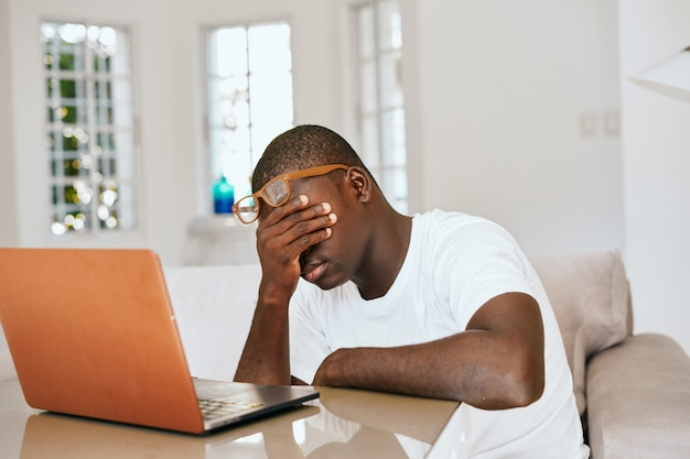 Männlicher afroamerikaner-freiberufler mit laptop zu hause