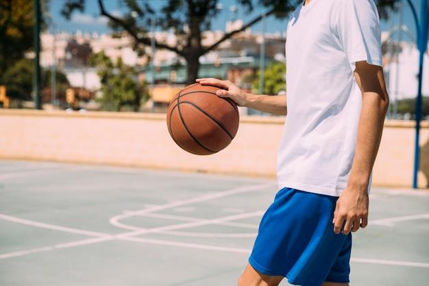 Männlicher anfüllender basketball der ernte draußen