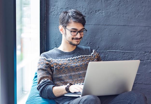Männlicher angestellter, der auf einem sofa nahe bei einem fenster mit seinem laptop sitzt