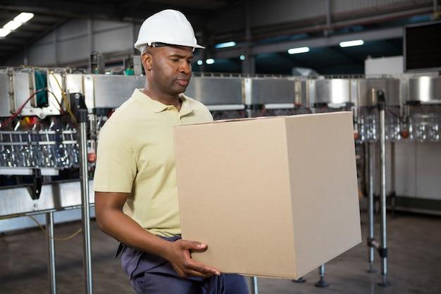Männlicher angestellter, der karton in saftfabrik trägt