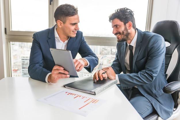 Männlicher angestellter, der seinem partner auf digitaler tablette in der sitzung darstellt