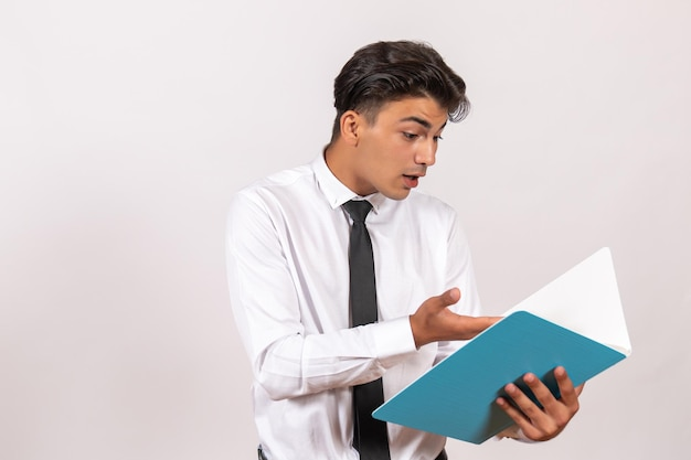 Männlicher angestellter der vorderansicht, der dokumente auf der weißen wand des männlichen geschäftsarbeitsjobs überprüft