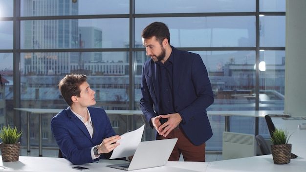 Männlicher angestellter des unternehmens bringt seinem chef finanzdokumente