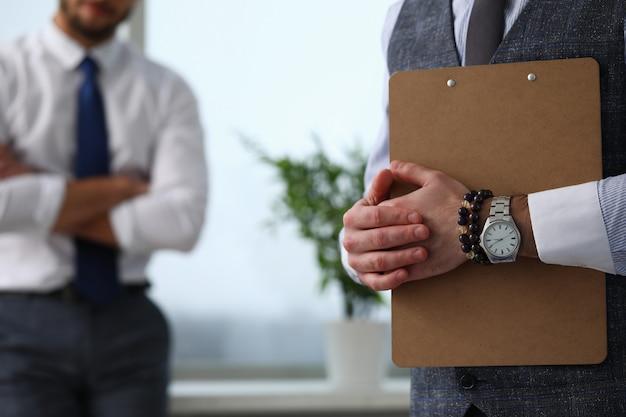 Männlicher angestellterarm, der papier im büro hält