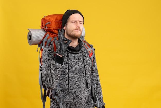 Männlicher anhalter mit lederhandschuhen und rucksack, der ein köstliches zeichen macht