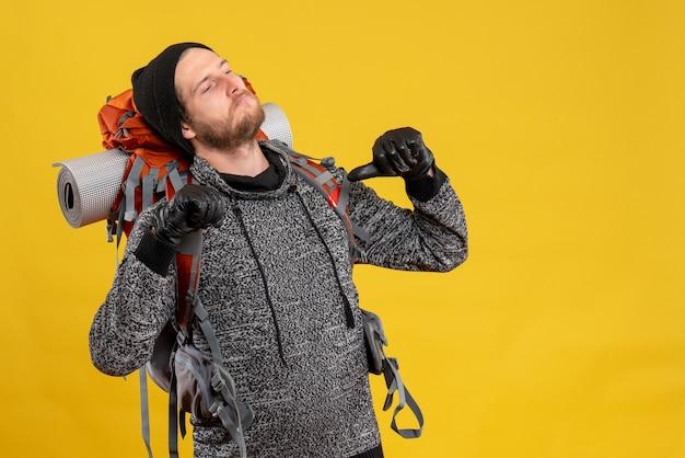 Männlicher anhalter mit lederhandschuhen und rucksack, der selbst mit den fingern zeigt