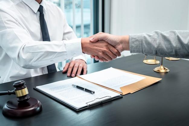 Männlicher anwalt, der dem kunden nach einer verhandlungszusammenarbeitssitzung im gerichtssaal die hände schüttelt