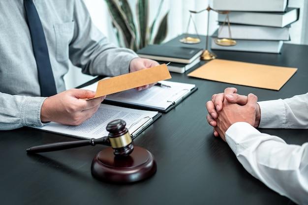 Männlicher anwalt, der verhandlungsrechtsfall mit kliententreffen mit dokumentkontakt im gerichtssaal bespricht