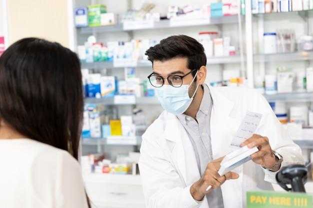 Männlicher apotheker aus dem nahen osten, der eine hygienische schutzmaske trägt, um eine infektion zu verhindern, indem er medikamente an verschreibungspflichtige patientinnen verkauft und in der modernen apotheke arzneimittelempfehlungen abgibt