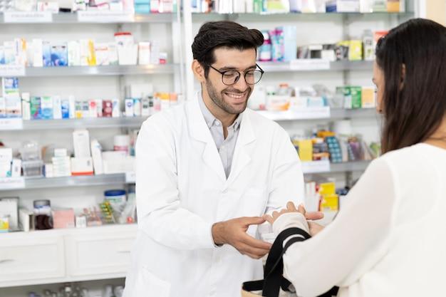 Männlicher apotheker aus dem nahen osten, der medikamente an verschreibungspflichtige patientinnen verkauft und in der modernen apotheke arzneimittelempfehlungen abgibt