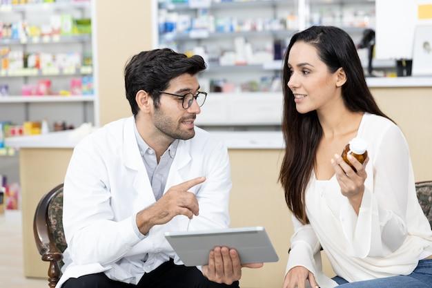 Männlicher apotheker aus dem nahen osten mit digitaler tablette, die medikamente an patientinnen verkauft und arzneimittelempfehlungen in der modernen apotheke abgibt