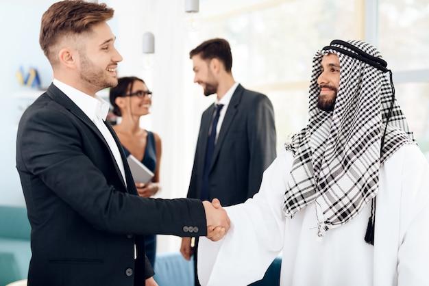 Männlicher araber und investor rütteln hände im büro.