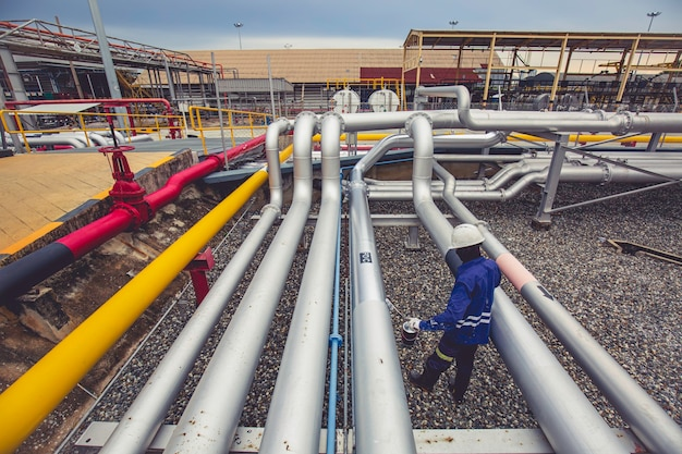 Männlicher arbeiter am pipeline-ölflussventil grau lackiert