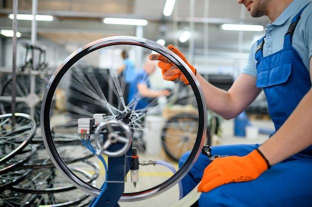 Männlicher arbeiter an der werkzeugmaschine überprüft fahrradfelge auf fabrik. montage der fahrradräder in der werkstatt, einbau der fahrradteile