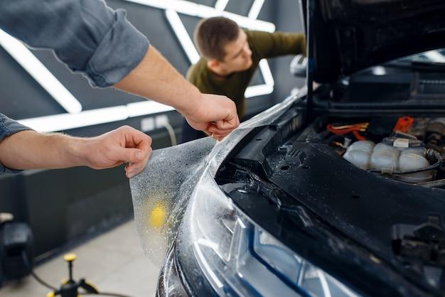 Männlicher arbeiter benetzt die oberfläche des autokotflügels mit spray, bevor er einen schutzfilm aufträgt. anbringen einer beschichtung, die den lack des autos vor kratzern schützt. neues fahrzeug in garage, detaillierung