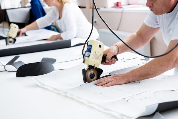 Männlicher arbeiter benutzt elektrische schneidemaschine. produktionslinie der textilindustrie.