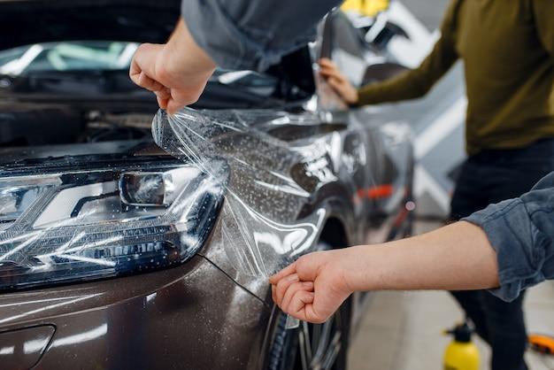 Männlicher arbeiter bringt autoschutzfolie auf den vorderen kotflügel an. anbringen einer beschichtung, die den lack des autos vor kratzern schützt. neufahrzeug in garage, tuning-vorgang
