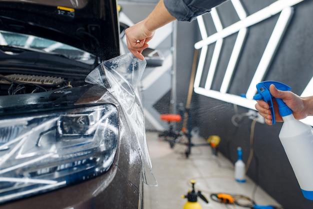 Männlicher arbeiter bringt autoschutzfolie auf den vorderen kotflügel an. anbringen einer beschichtung, die den lack des autos vor kratzern schützt. neufahrzeug in garage, tuning