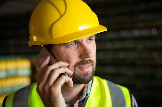 Männlicher arbeiter, der am telefon in der fabrik spricht